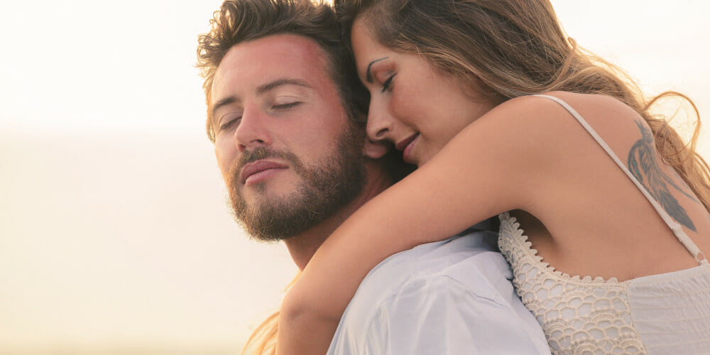 Portrait of a woman embracing her man from behind on sunset background