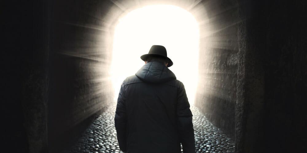 Man walking into light